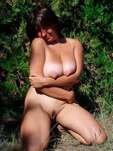 Пышная зрелая дама позирует на природе